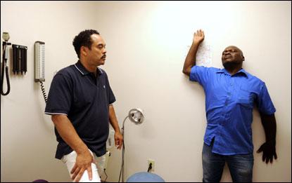 Winston-Salem Journal Photo by Jennifer Rotenizer, of Alex Stovall (left) working with clinic patient Henry Byrd.