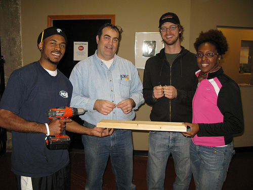Fellows worked with StreetWise Executive Director Bruce Crane (second from left) to repair and replace the organization's bathroom countertops.